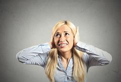stressed woman covering her ears - stock photo