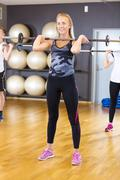 Smiling woman in group doing squat exercises at fitness gym Kuvituskuvat
