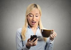 woman reading good news on smart phone - stock photo