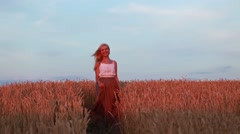 Young beautiful woman walking in a wheat field. Hand of a young girl touching - stock footage