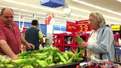 People looking for fresh corn inside Walmart store Stock Footage