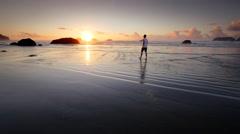 Teen boy walking on beach, Pacific Coast, Oregon - stock footage