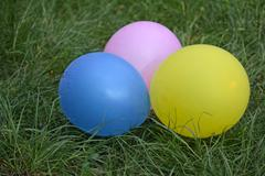Multicolored balloons lying on green grass. Holidays Stock Photos