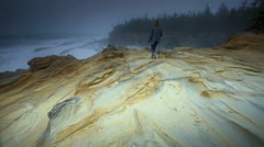 Woman walking among sandstone formations by Pacific Coast, OR Stock Footage