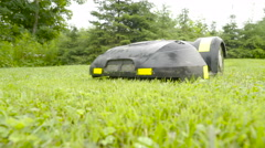 The black and yellow automower on the grass Stock Footage