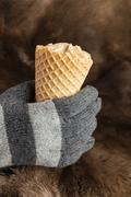 Hands in knitted gloves keep ice cream - stock photo