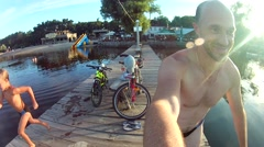 Peopie jumps off a wooden dock into the water . Stock Footage