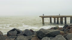 Granite rocks. Metall pier with bollard and bitt in rough sea Stock Footage