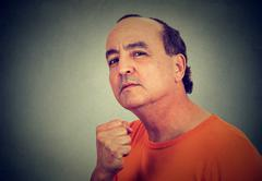 Portrait of angry man threatening someone with fist - stock photo