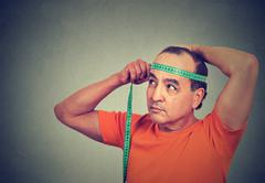 Closeup middle aged man measuring diameter of his head Stock Photos
