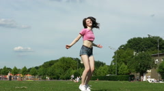Happy girls in short shorts jump in slow motion Stock Footage