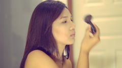 Young Asian Woman applying powder with big brush. Toned video Stock Footage