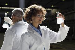 African scientists examining beakers of liquid in factory Stock Photos