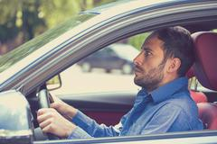 Scared funny looking young man driver in the car. Human emotion face expressi Stock Photos