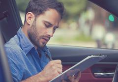 transportation ownership concept. Man inside new car reading signing document - stock photo