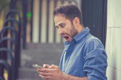 Closeup portrait anxious young man looking at phone seeing bad news message o - stock photo