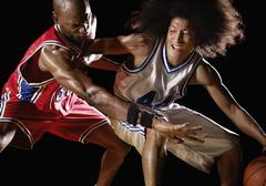 Multi-ethnic basketball players competing for basketball Stock Photos