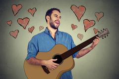 Portrait handsome musician young man in love playing guitar and singing a son Stock Photos