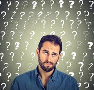 Funny confused skeptical man thinking looking up has many questions Stock Photos