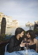 Italian couple drinking red wine at sidewalk cafe Stock Photos