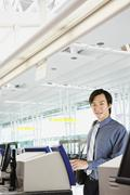 Asian businessman checking in at airport Stock Photos