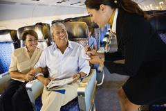 Flight attendant helping couple on airplane Stock Photos