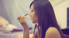 Young Asian Woman looking in mirror and applying cosmetics 4k UHD (3840x2160) Stock Footage