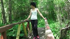 Attractive woman walk over forest wooden bridge Stock Footage