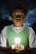 African boy holding glowing cfl lightbulb Stock Photos