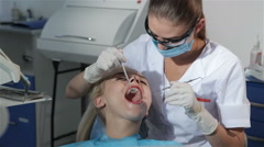 Dental surgeon applies dental probe to examine patient's teeth - stock footage