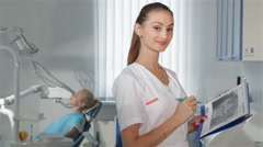Female dentist poses at the dental clinic - stock footage