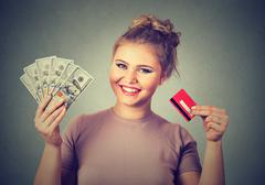 Woman shopping holding showing credit card and cash dollar banknotes bills Stock Photos