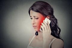 Concerned young woman talking on mobile phone having pain headache - stock photo
