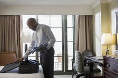 African businessman in hotel packing suitcase Kuvituskuvat