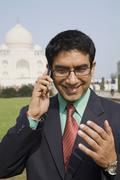 Indian businessman talking on cell phone at the Taj Mahal Kuvituskuvat