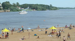 People swimming and sunbathing on the sand beach Stock Footage