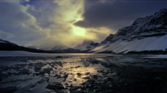 Lake with ice reflecting snow covered mountains, Banff, NP, Canada Stock Footage