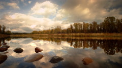 Pond with rocks reflecting autumn colors, Grand Teton NP, WY Stock Footage