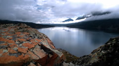 Rocks with lichen and mountain lake, Glacier, NP, MT Stock Footage