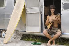 Pacific Islander man playing ukulele Kuvituskuvat