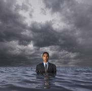 Hispanic businessman standing in water Stock Photos