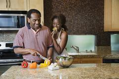 African couple fixing healthy meal in modern kitchen Stock Photos