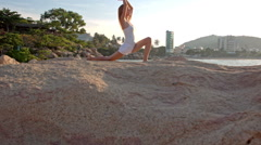 Blond Girl Stands in Yoga Pose Bent Leg on Rocky Beach Stock Footage