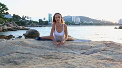 Blond Girl Sits in Yoga Pose Lotus on Rocky Beach Stock Footage