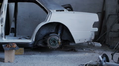 Frame of the not worked car in the garage where girl legs appear Stock Footage