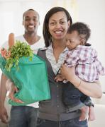 African couple holding baby and groceries in reusable bag Stock Photos