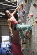 Mixed race woman indoor rock climbing Kuvituskuvat