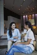 Hispanic women drinking white wine in hotel lobby Stock Photos