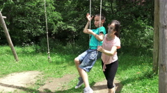 Beautiful boy on the swing in the forest playground park Stock Footage