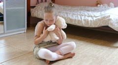 Girl is hugging and comforting white teddy bear. Stock Footage